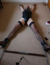 self-bondage in shiny swimsuit, stockings and high heels.